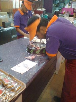 カウンターでケーキのメッセージを書くバングラデシュkingsの店員